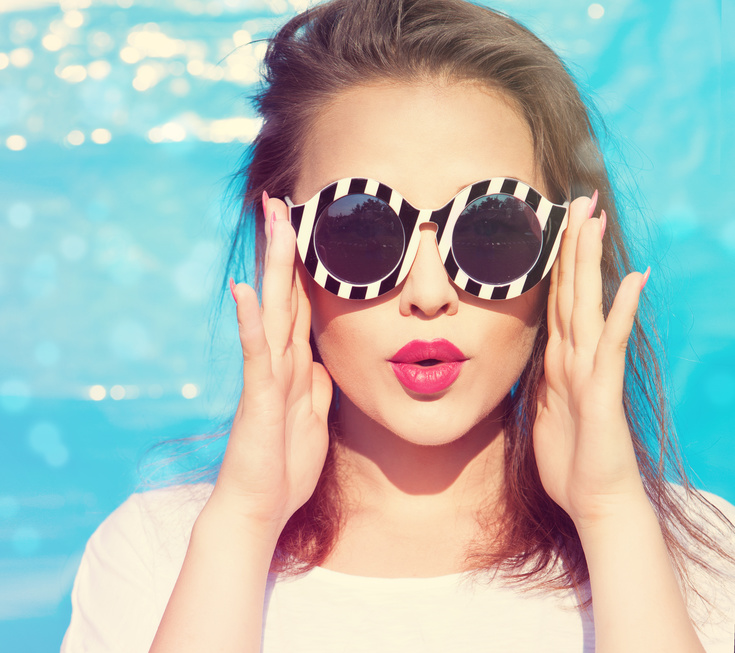 Colorful portrait of young attractive surprised woman wearing sunglasses. Summer beauty  concept